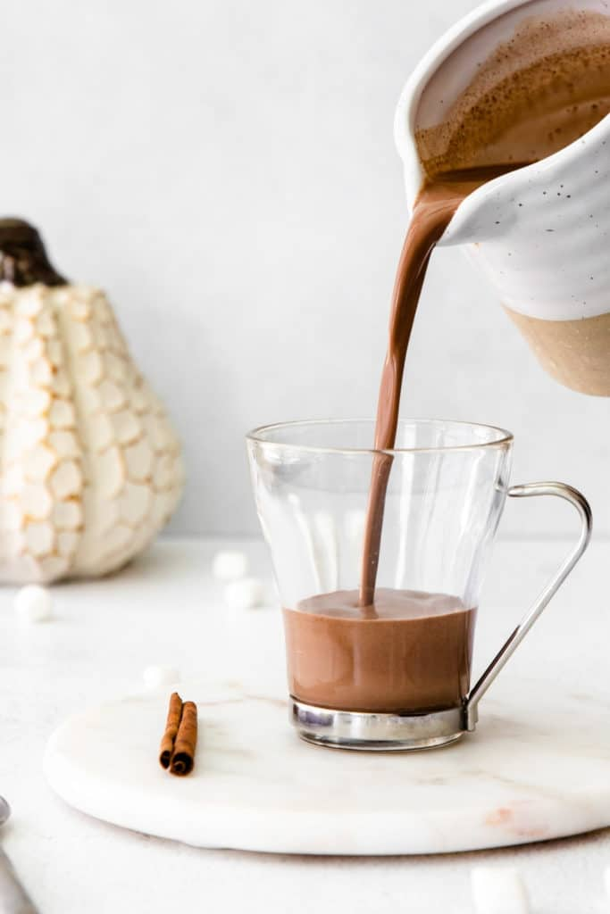Pumpkin spice hot cocoa being poured into a clear-glass mug from a ceramic pitcher.