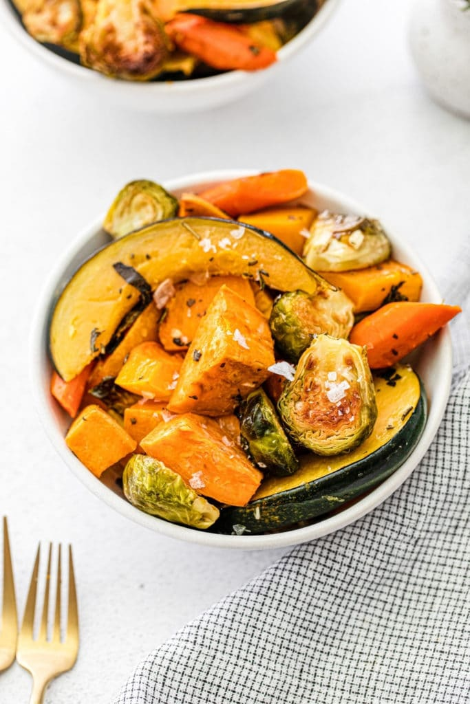 Serving bowl of roasted fall vegetables on a dinner table.
