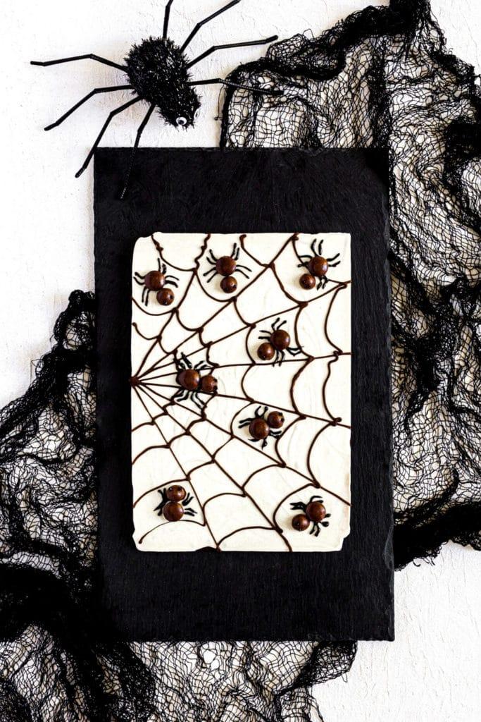 Unsliced slab of Spiderweb Chocolate Bark (AKA Halloween Bark) on a black slate serving board.