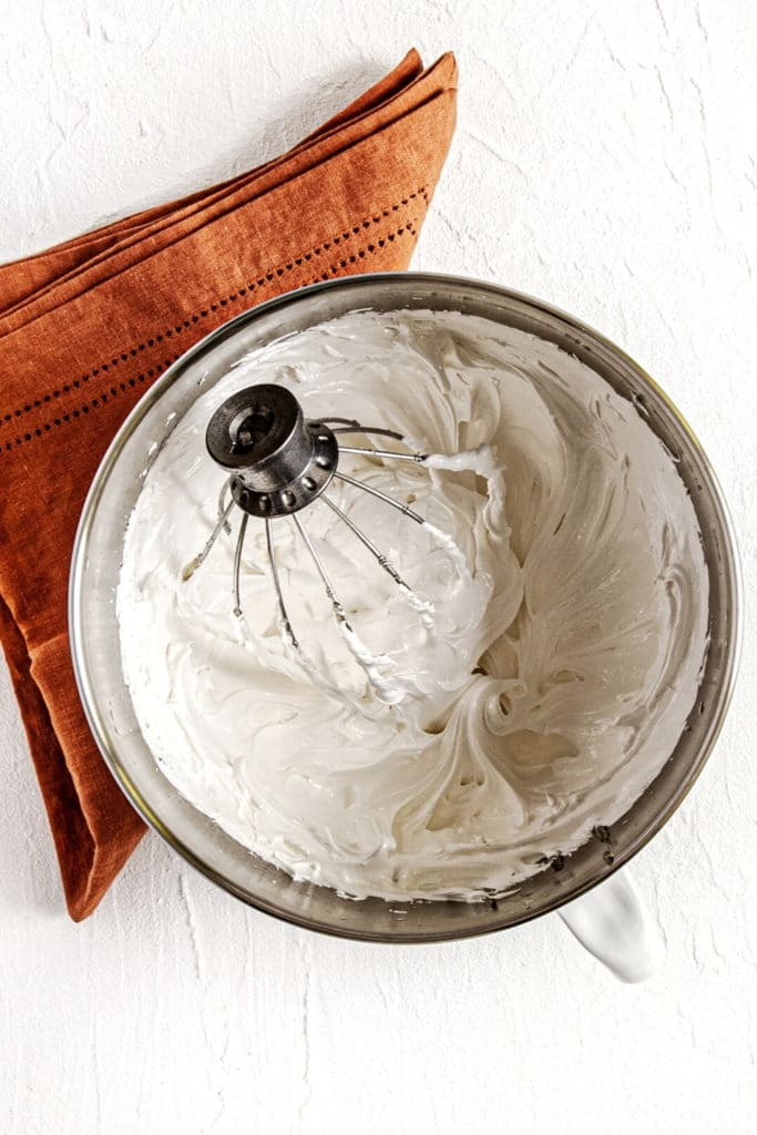 Homemade marshmallow fluff topping for sweet potato casserole in a mixing bowl with metal whisk.