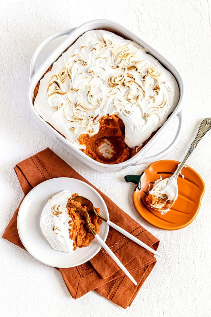 Sweet Potato Fluff Casserole in a white baking dish plus a serving with spoon and fork.