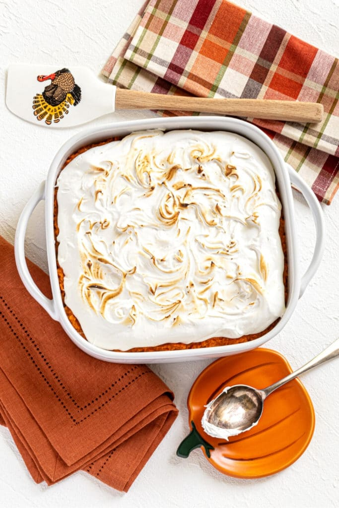 White baking dish with sweet potato fluff casserole on a Thanksgiving serving table with spoon.