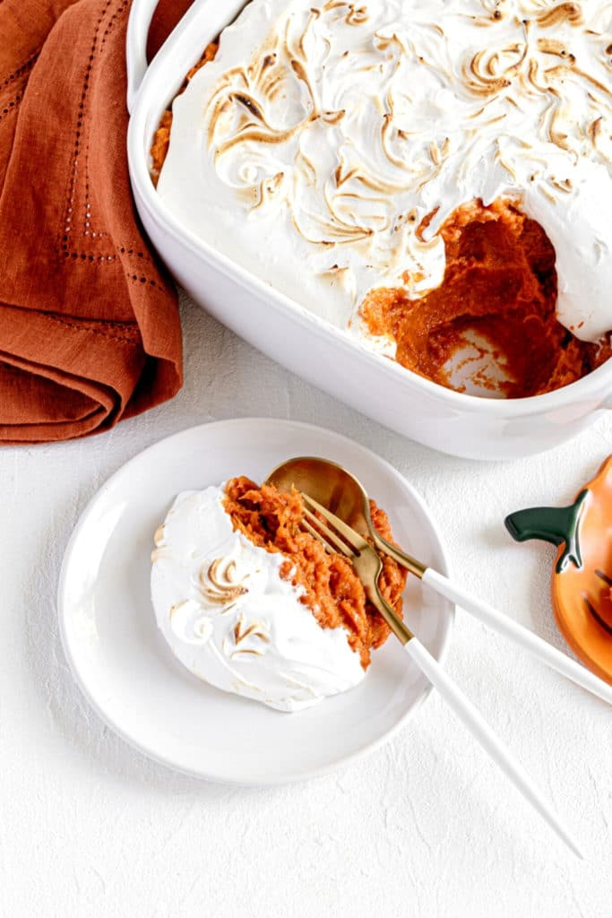 Serving of baked sweet potato fluff casserole on plate with utensils, next to baking dish.