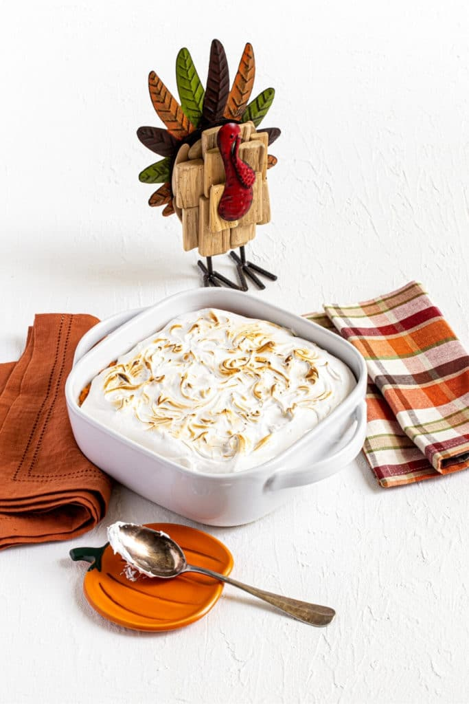 Baked sweet potato fluff casserole on a white Thanksgiving tabletop with turkey decoration.