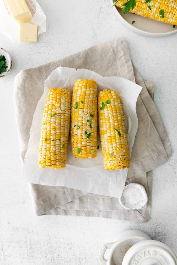 Four air fryer corn on the cob garnished with butter, salt and parsley on a serving table.