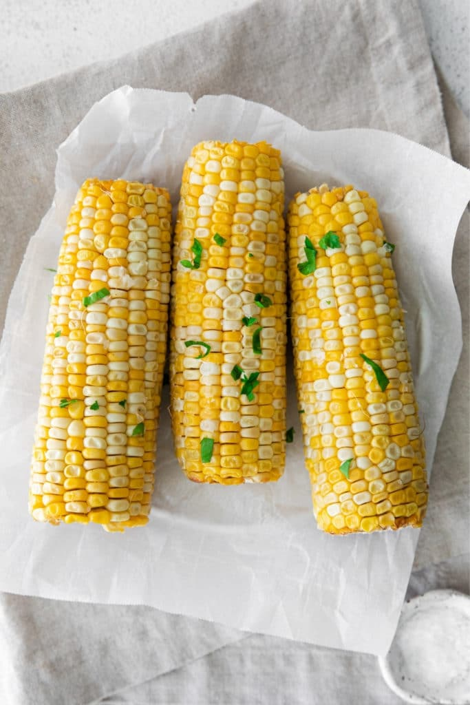 Three cobs of air fryer corn cooked to perfection with salt and parsley garnishes.
