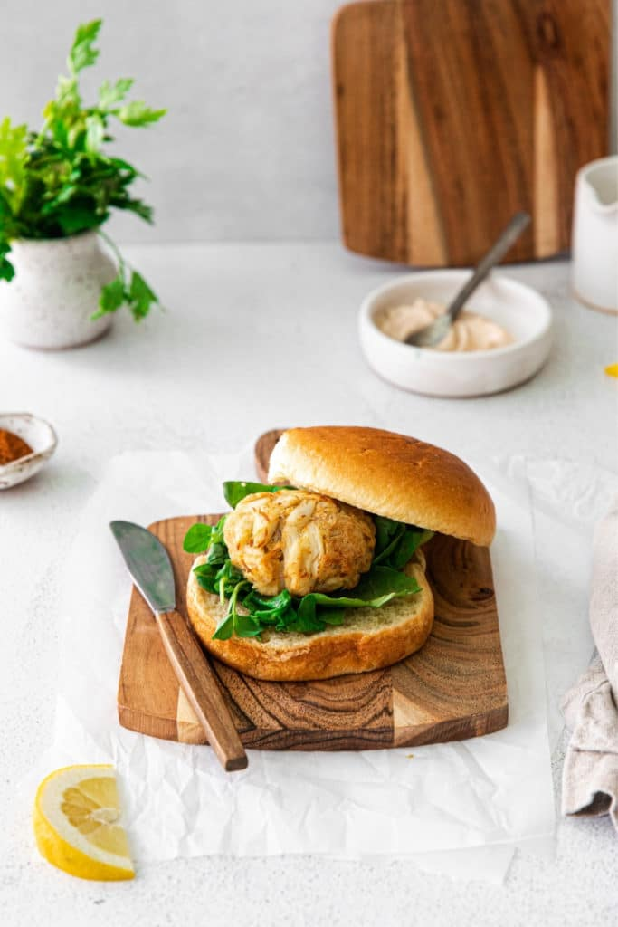 Crab cake sandwich on a wooden board with knife, chipotle mayo spread, and slice of lemon.