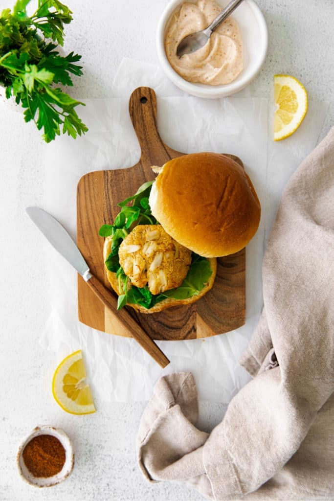 Overhead view of air fryer crab cake sandwich on a bun with produce, spread and lemon.