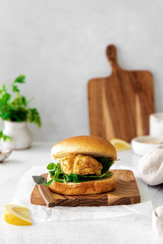 Air fryer crab cake sandwich on a wooden board with knife and wedge of juicy lemon.