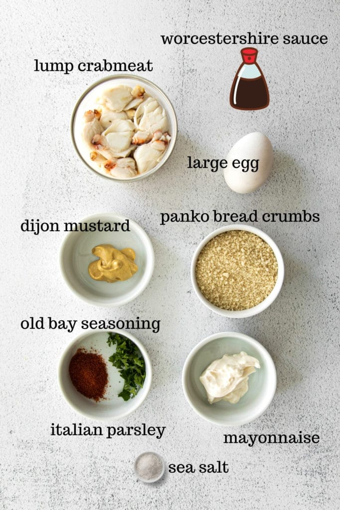 Crab cake ingredients measured out in small dishes on the countertop.