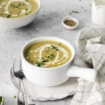 A serving of Cream of Asparagus Soup garnished with a swirl of heavy cream and sprinkling of chives.