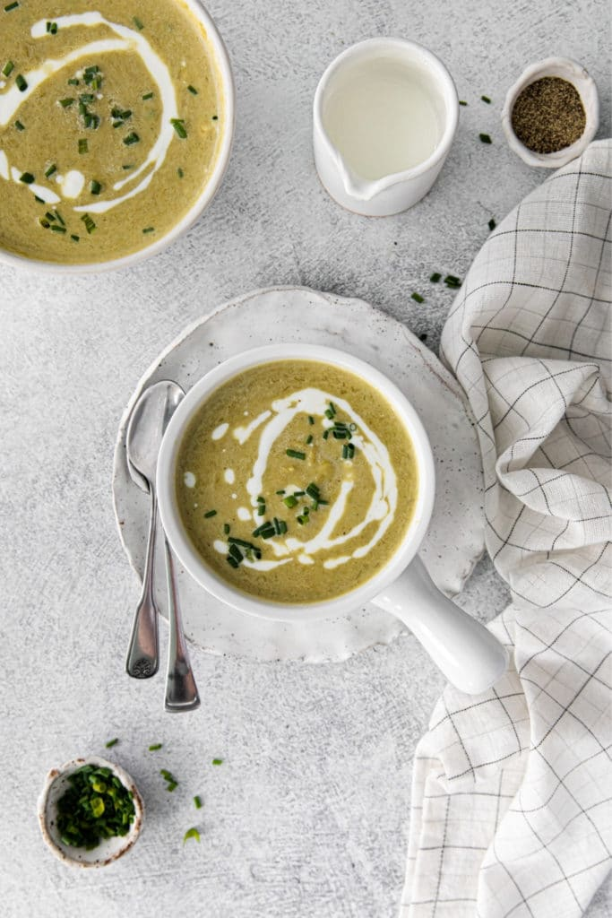 Two bowls of creamy asparagus soup with garnishes of black pepper, heavy cream and chopped chives.