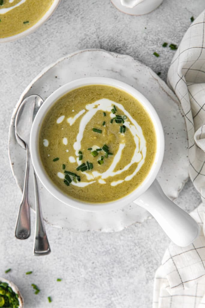 Creamy asparagus soup garnished with drizzles of heavy cream and freshly-snipped chives.