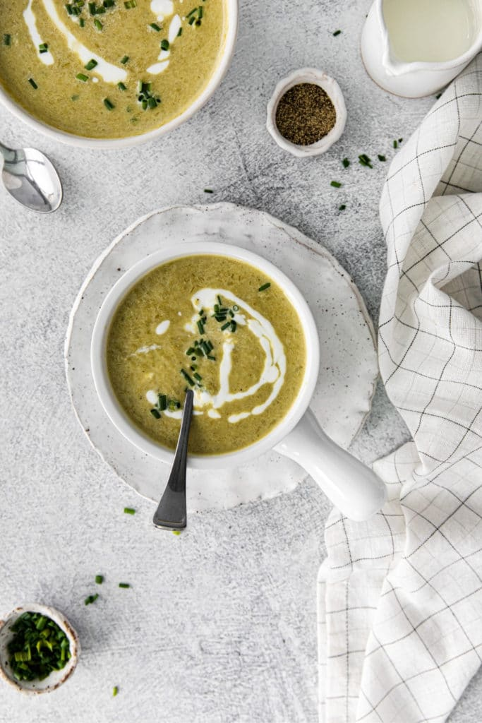 Serving of healthy asparagus soup in a white bowl with metal spoon.