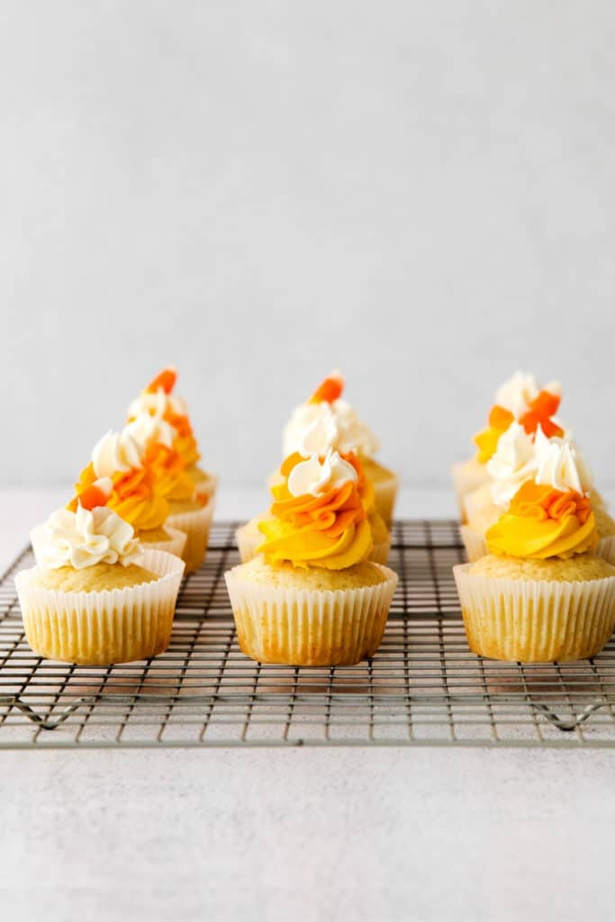 Nine frosted candy corn cupcakes on a metal rack.