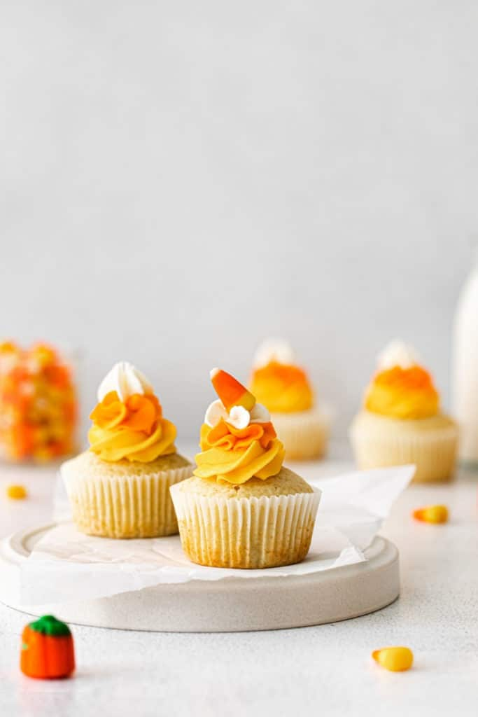 Candy corn cupcakes with swirls of multi-color frosting on a Halloween dessert table.