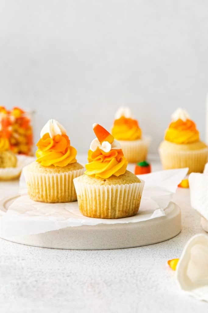 Vanilla Halloween cupcakes with swirled white/orange/yellow frosting garnished with candy corn.