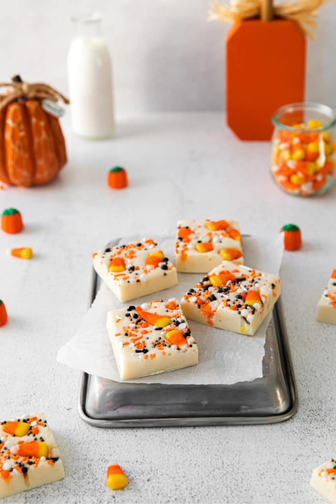 Four squares of Halloween candy corn fudge sitting on a small metal tray on a decorated dessert table.