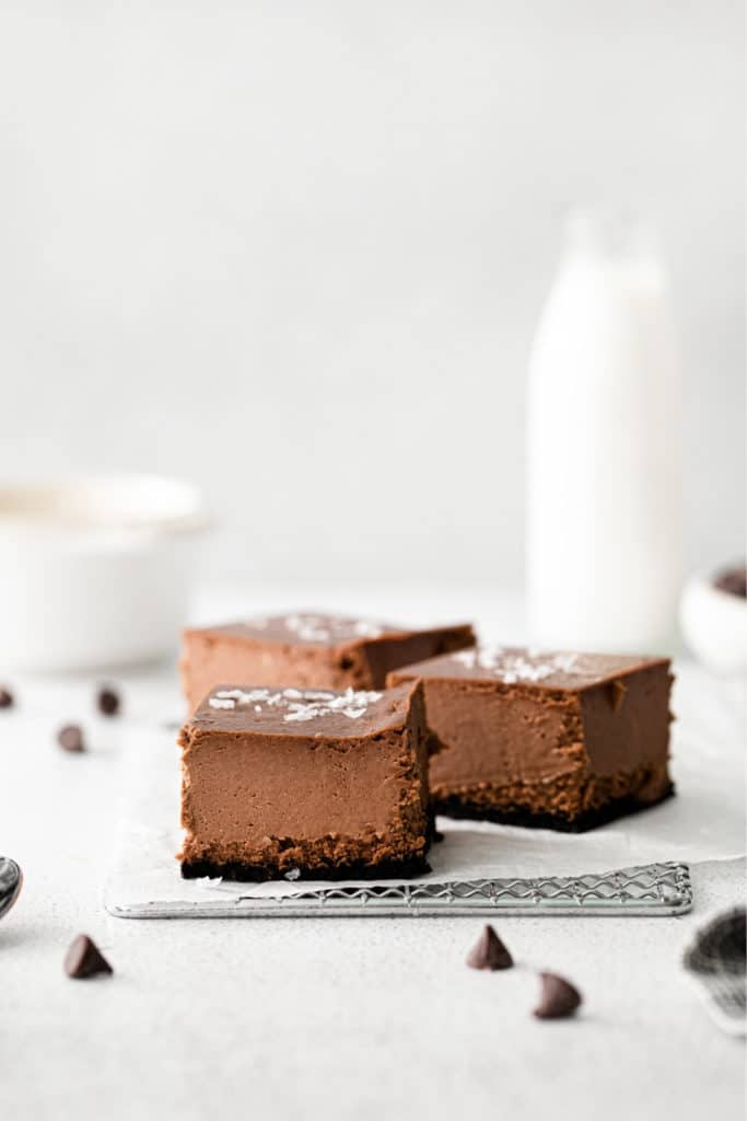 Squares of chocolate cheesecake with Oreo cookie crust sitting atop a parchment-paper-lined metal rack.