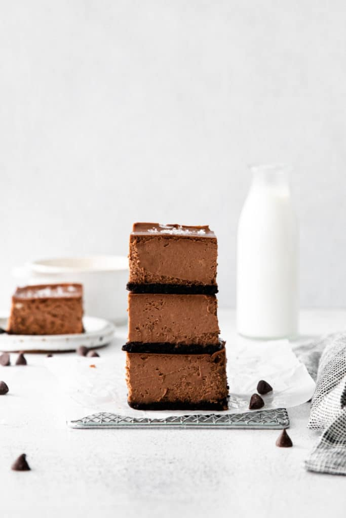 Three chocolate chip cheesecake bars stacked on a metal rack next to a glass bottle of milk.