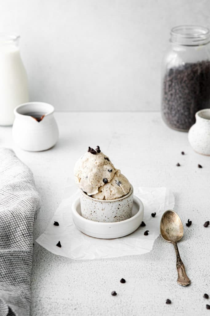 Two scoops of homemade chocolate chip ice cream flavored with mocha in a ramekin with spoon.