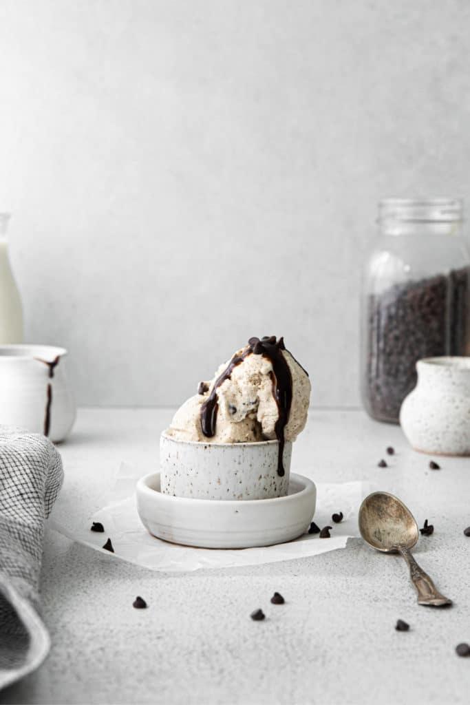 Chocolate chip ice cream in a ramekin garnished with hot fudge and mini chocolate chips.