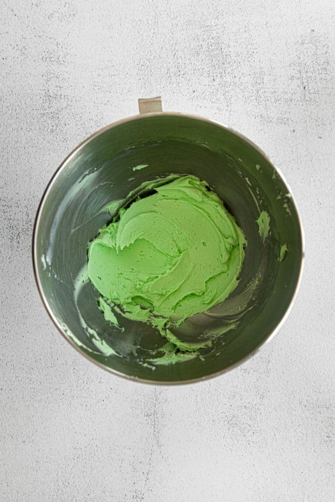 Mint frosting whipped in the bowl of a stand mixer.