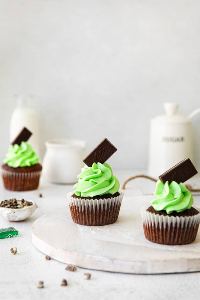 Three mint chocolate cupcakes with mint buttercream frosting.