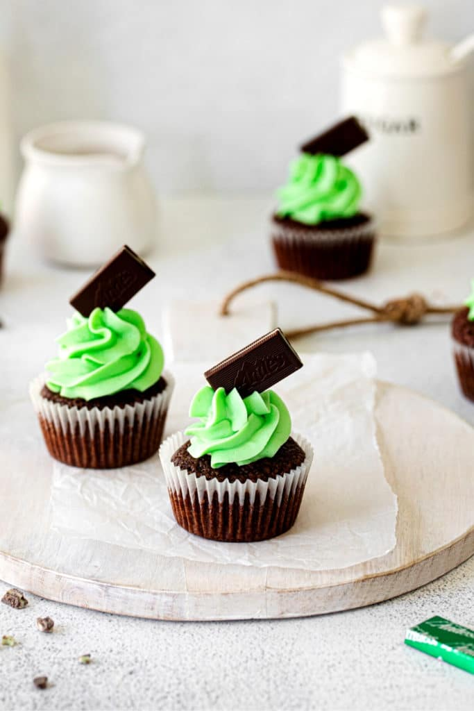 A dessert table with mint chocolate cupcakes with mint buttercream frosting garnished with Andes mints.
