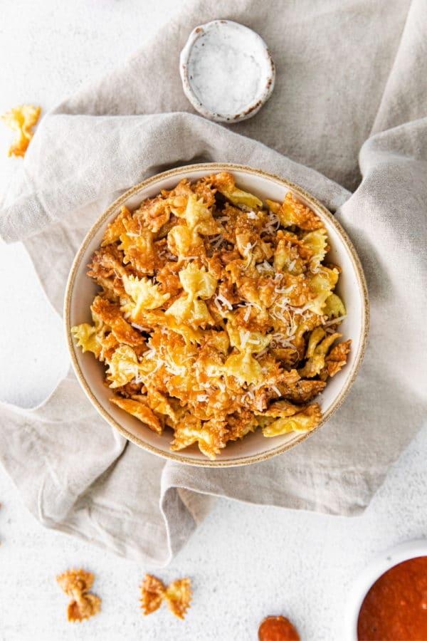 Garlic-parmesan pasta chips in a bowl alongside marinara dipping sauce.