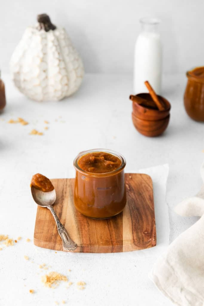 Jar of pumpkin butter with metal spoon on a serving table.