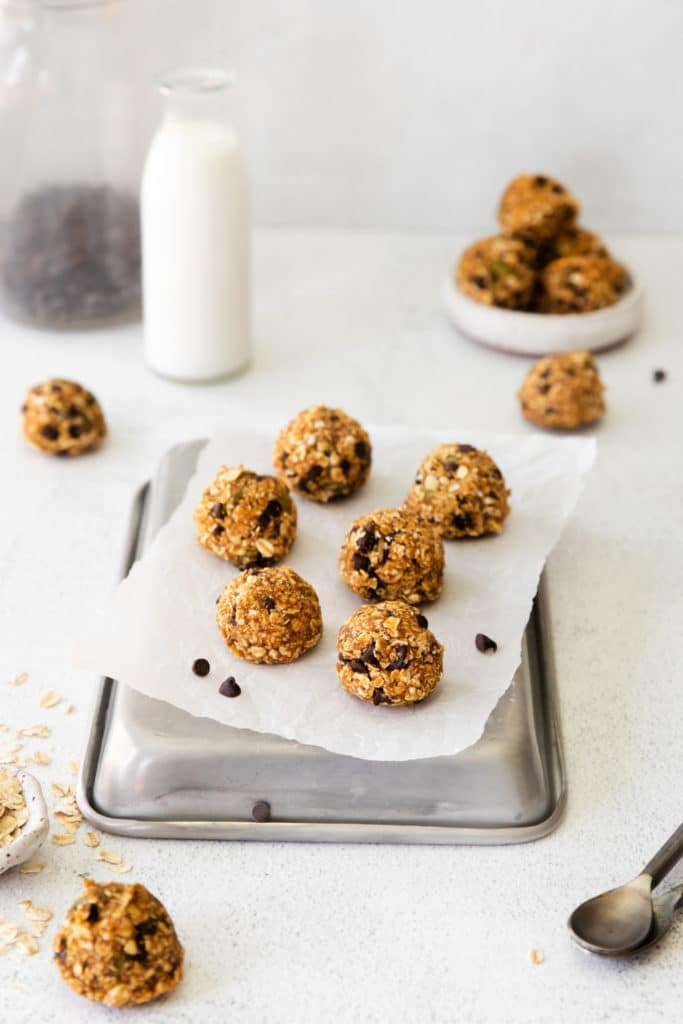 One dozen pumpkin energy balls with oats and chocolate chips on a snack table with milk.