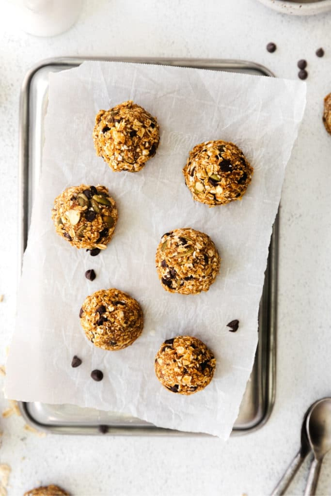 Half dozen chilled and set pumpkin energy balls served on a table ready for snacking.