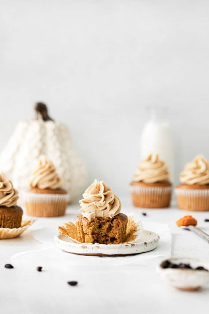 A pumpkin spice latte cupcake unwrapped on a plate with a bite taken out.