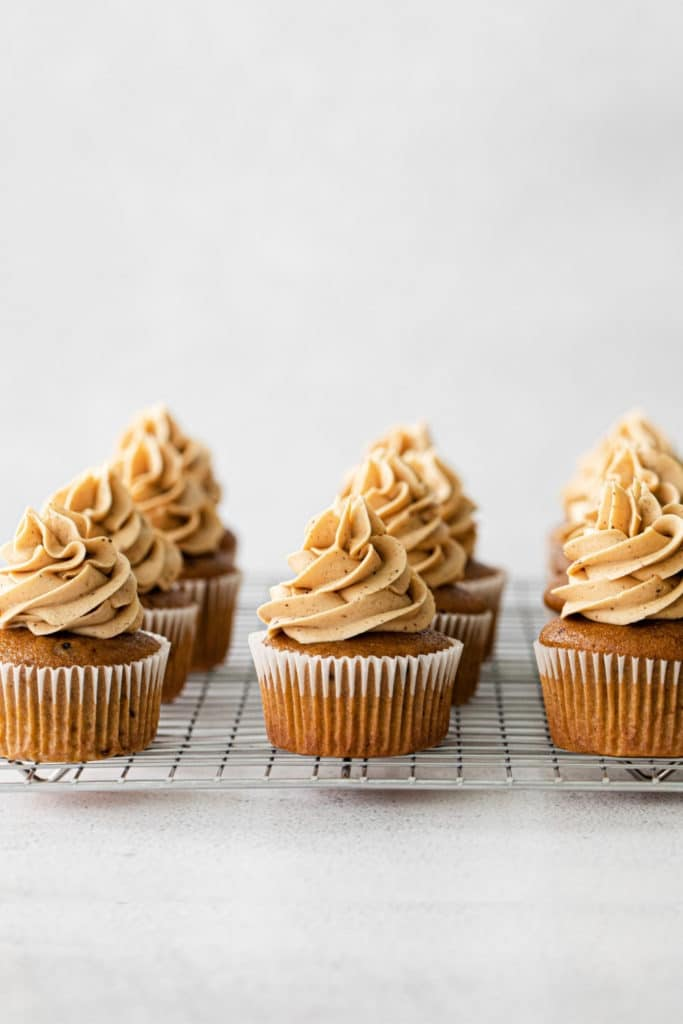 Freshly frosted pumpkin spice cupcakes on a metal rack.