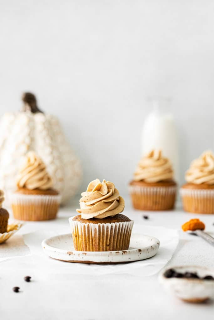 Five pumpkin Spice Cupcakes on a dessert table with a glass bottle of milk.