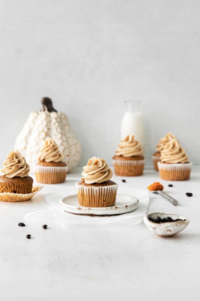 Five pumpkin spice cupcake with swirls of vanilla espresso frosting on a dessert table.