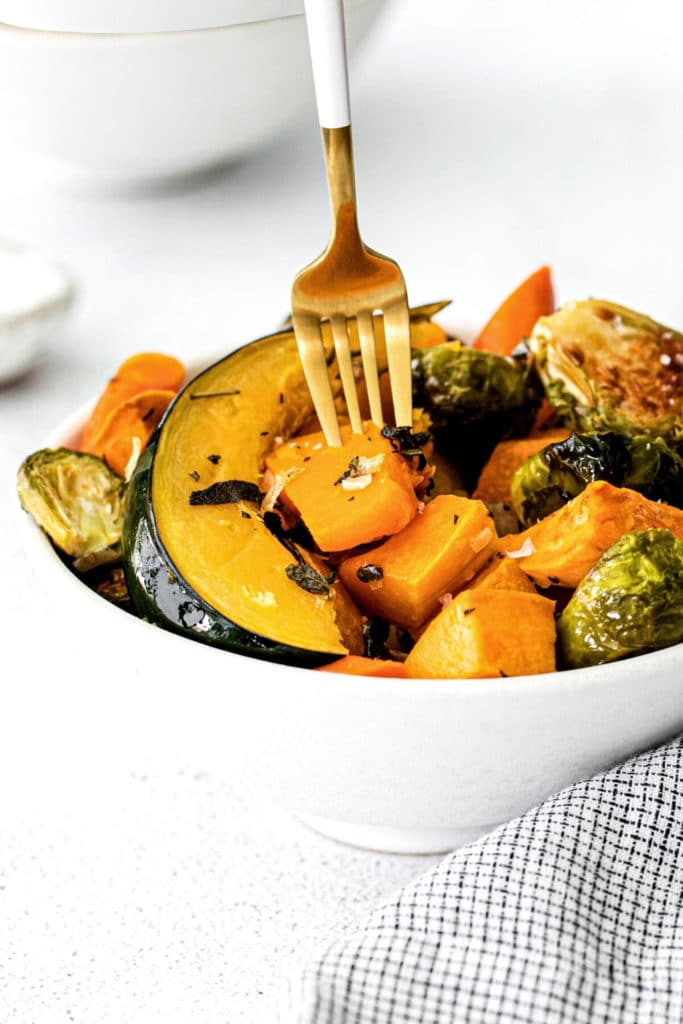 A gold fork piercing the tender flesh of roasted fall vegetables in a white bowl.