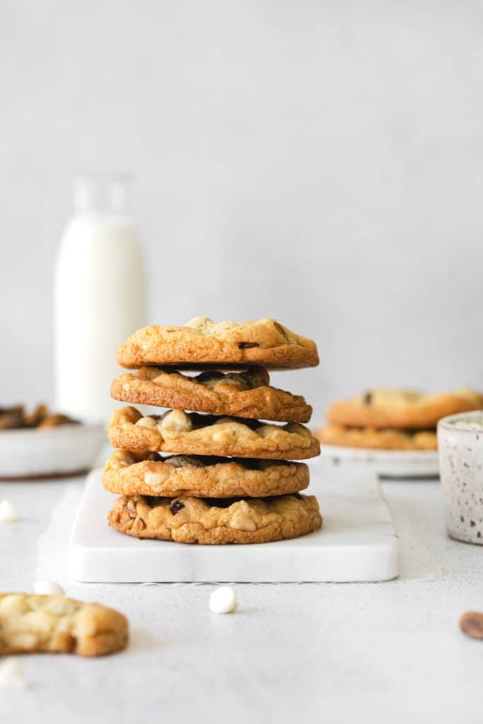 Stack of 5 white chocolate chip cookies on a white marble board.