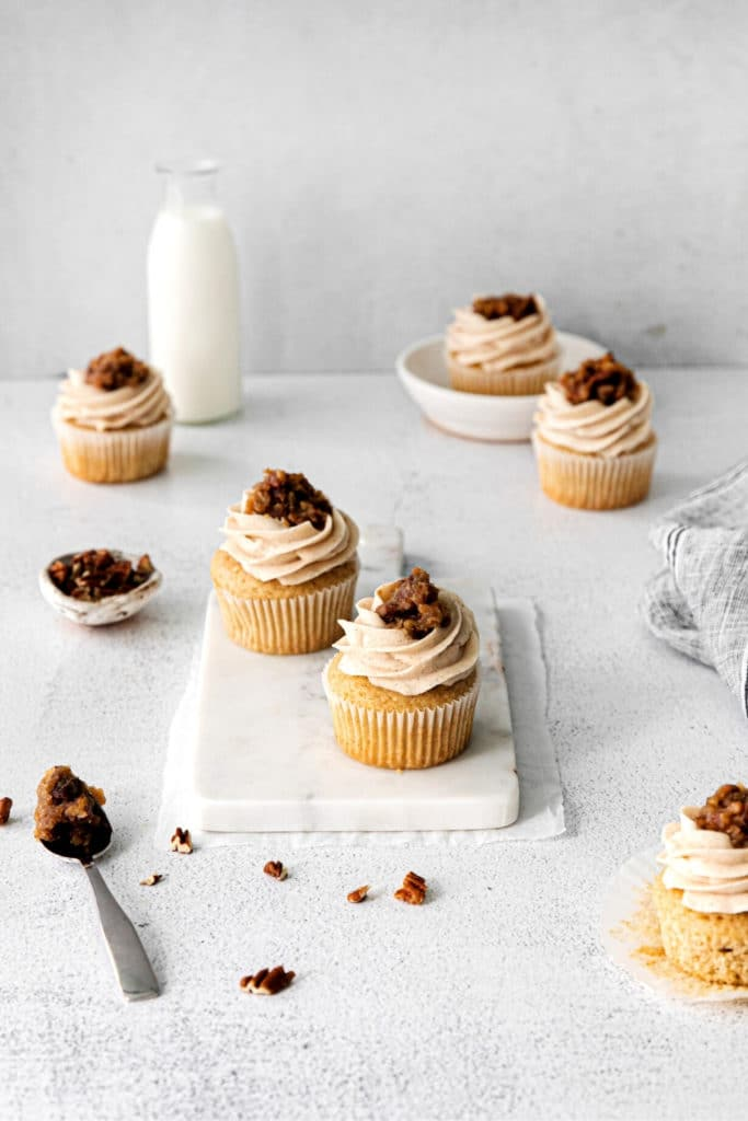 Thanksgiving cupcakes being frosted and topped with a delicious butter pecan garnish.