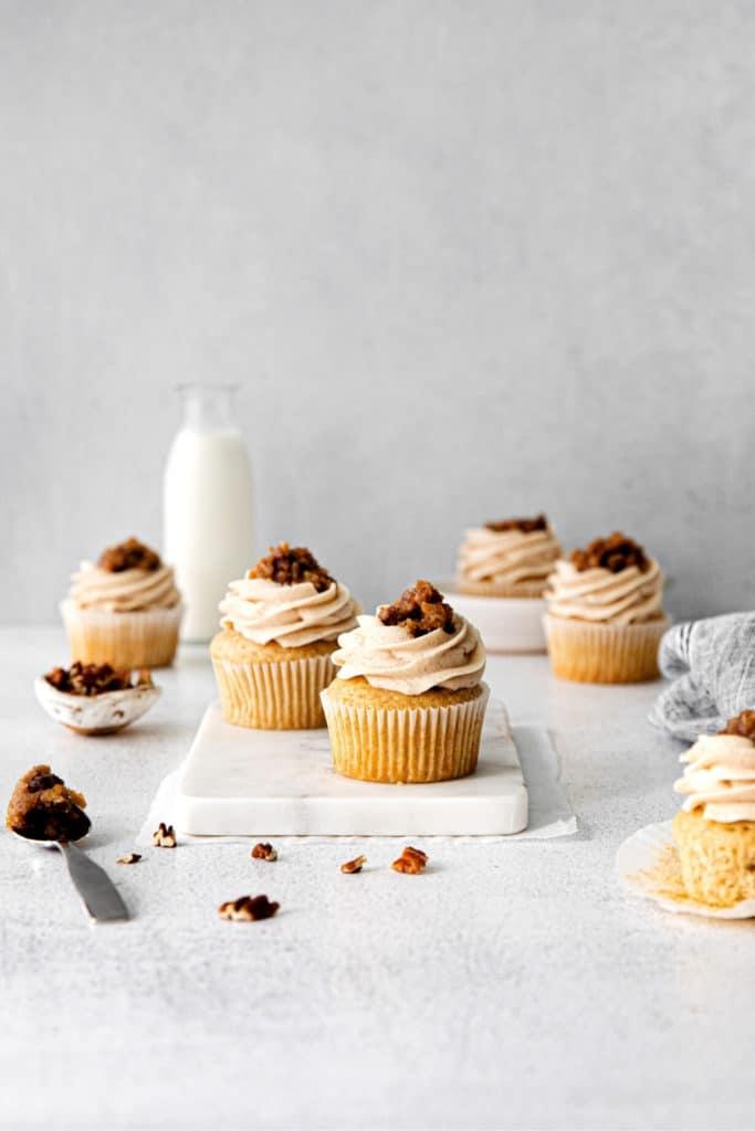 Half dozen butter pecan cupcakes (AKA: pecan pie cupcakes) on a dessert table with milk.