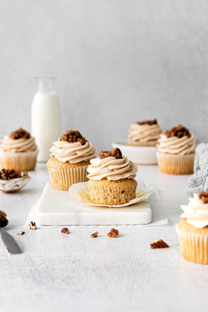 Freshly-frosted butter pecan cupcakes on a dessert table with milk.