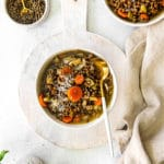 Green lentil soup on a serving table with Parmesan cheese and Italian parsley.