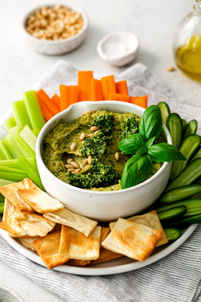 Appetizer table with pesto hummus garnished with pine nuts and a fresh leaf of basil.