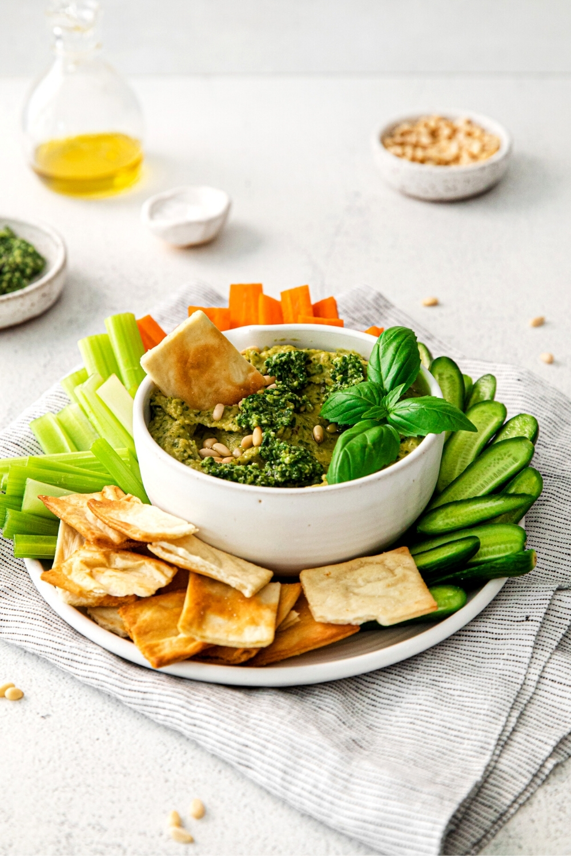 Basil Pesto hummus dip served with crackers and veggies.