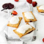Three homemade strawberry pop tarts cooling on the back of a parchment paper-lined metal tray.