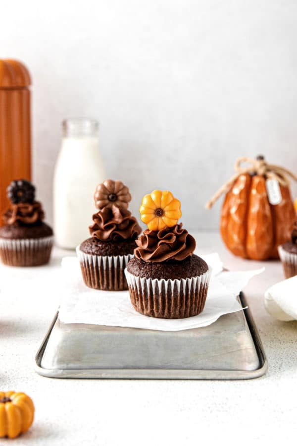 Three chocolate-pumpkin Thanksgiving cupcakes with chocolate buttercream frosting and decorative pumpkin cupcake toppers.